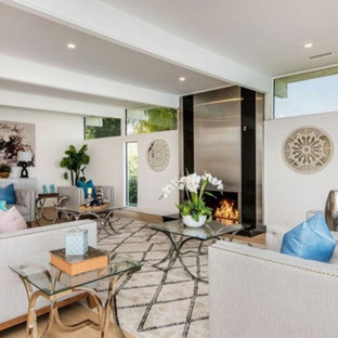 Inspiration for a large modern open concept light wood floor and brown floor living room remodel in Los Angeles with white walls and a standard fireplace