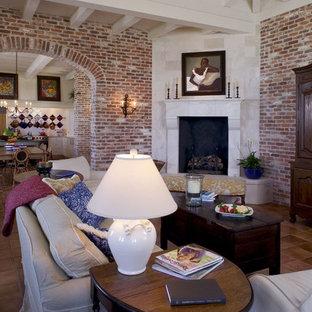 Idee per un grande soggiorno tropicale aperto con pavimento in terracotta, camino ad angolo, cornice del camino in pietra e TV nascosta
