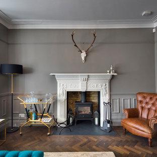 Diseño de salón cerrado, tradicional renovado, de tamaño medio, sin televisor, con paredes marrones, suelo de madera oscura, suelo marrón y estufa de leña