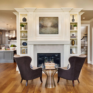 Inspiration for a large timeless medium tone wood floor living room remodel in Portland with gray walls, a standard fireplace and a stone fireplace