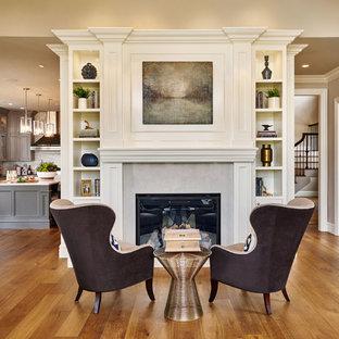 Foto di un grande soggiorno classico con pareti grigie, pavimento in legno massello medio, camino classico e cornice del camino in pietra