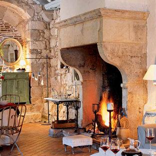 ニューヨークの大きい地中海スタイルのおしゃれなLDK (ベージュの壁、テラコッタタイルの床、標準型暖炉、石材の暖炉まわり、テレビなし) の写真
