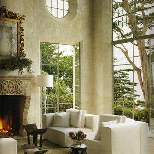 ロサンゼルスの広い地中海スタイルのおしゃれなLDK (フォーマル、マルチカラーの壁、ライムストーンの床、標準型暖炉、石材の暖炉まわり、テレビなし) の写真
