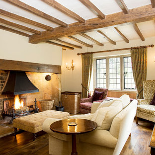 Photo of a country living room in Oxfordshire with beige walls, medium hardwood flooring, a standard fireplace, a brick fireplace surround and brown floors.