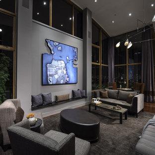 На фото: большая открытая гостиная комната в современном стиле с серыми стенами, темным паркетным полом и коричневым полом без камина с