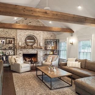 Example of a cottage dark wood floor and brown floor living room design in New York with white walls, a standard fireplace and a brick fireplace