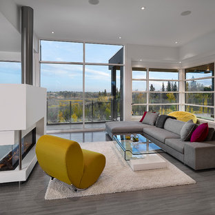 Inspiration for a modern open concept gray floor living room remodel in Edmonton with white walls and a two-sided fireplace