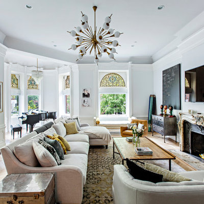 Living room - large eclectic open concept medium tone wood floor and brown floor living room idea in New York with white walls, a standard fireplace, a metal fireplace, a wall-mounted tv and a music area