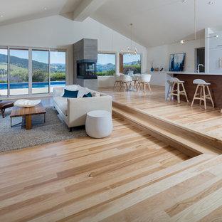 Modern inredning av ett stort allrum med öppen planlösning, med vita väggar, ljust trägolv, ett finrum, en dubbelsidig öppen spis, en spiselkrans i metall och beiget golv