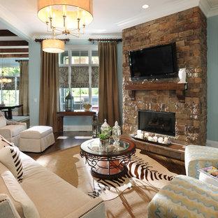 ナッシュビルのトラディショナルスタイルのおしゃれなリビング (青い壁、石材の暖炉まわり、壁掛け型テレビ) の写真