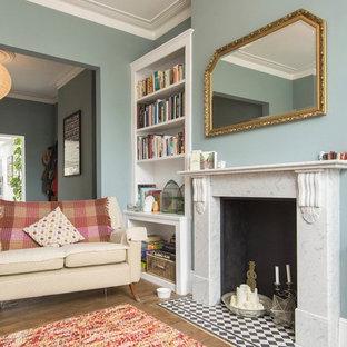ヴィクトリアン調のおしゃれなリビング (青い壁、無垢フローリング、標準型暖炉、茶色い床) の写真