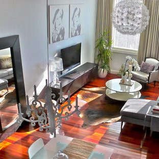 Diseño de salón minimalista, pequeño, con paredes blancas y televisor colgado en la pared