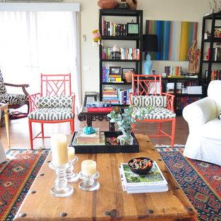 Modelo de salón para visitas abierto, ecléctico, grande, sin chimenea, con paredes beige, suelo de madera en tonos medios, televisor retractable y suelo marrón