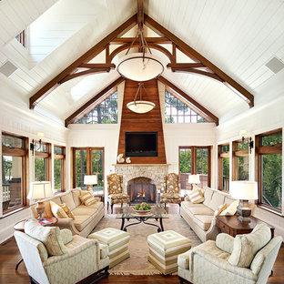 Exemple d'un très grand salon bord de mer ouvert avec un mur blanc, un sol en bois foncé, une cheminée standard et un manteau de cheminée en pierre.