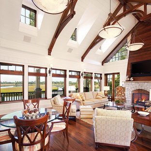 Coastal open concept dark wood floor living room photo in Charleston with white walls, a standard fireplace and a stone fireplace