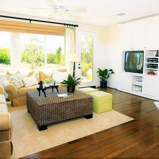 リッチモンドの大きいトロピカルスタイルのおしゃれな独立型リビング (ベージュの壁、濃色無垢フローリング、コーナー設置型暖炉、木材の暖炉まわり、据え置き型テレビ、白い床) の写真