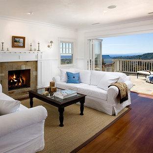 Cette photo montre un grand salon bord de mer ouvert avec un mur blanc, un sol en bois brun, une cheminée standard et un manteau de cheminée en pierre.