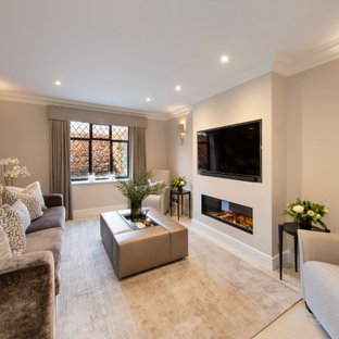 Design ideas for a large traditional formal enclosed living room in Surrey with carpet, a standard fireplace, beige floors, a wall mounted tv and beige walls.