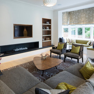 Contemporary formal living room in London with white walls, light hardwood flooring, a ribbon fireplace and a wall mounted tv.