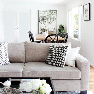 シドニーの広いビーチスタイルのおしゃれなLDK (白い壁、濃色無垢フローリング、標準型暖炉、石材の暖炉まわり、据え置き型テレビ、マルチカラーの床) の写真