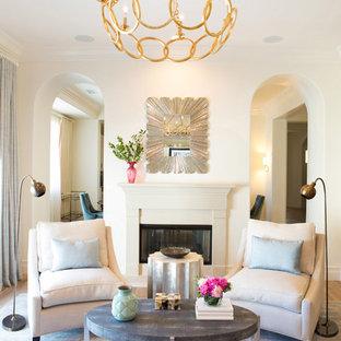 Modelo de salón para visitas cerrado, clásico renovado, grande, con paredes blancas, suelo de madera en tonos medios, chimenea tradicional y marco de chimenea de piedra