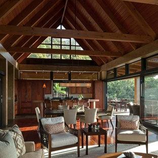Immagine di un grande soggiorno tropicale aperto con pareti beige, parquet scuro, camino classico, cornice del camino in intonaco, nessuna TV e pavimento marrone