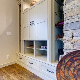 Idee per un soggiorno stile americano di medie dimensioni e aperto con pareti beige, pavimento in legno massello medio, camino classico, cornice del camino in pietra e TV nascosta