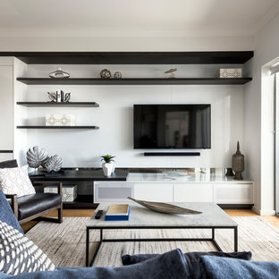 This is an example of a small contemporary formal open concept living room in Perth with grey walls, light hardwood floors, a wall-mounted tv and beige floor.