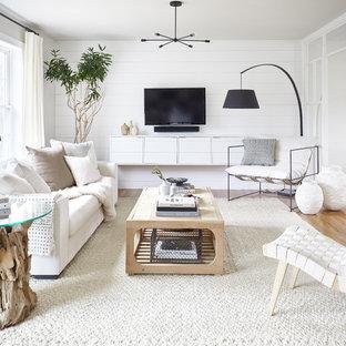 Ejemplo de salón abierto, campestre, pequeño, sin chimenea, con paredes blancas, suelo marrón, suelo de madera en tonos medios y televisor colgado en la pared