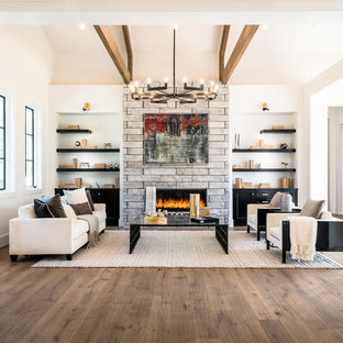 Example of a trendy formal and open concept medium tone wood floor and brown floor living room design in Los Angeles with white walls, a ribbon fireplace, a stone fireplace and no tv