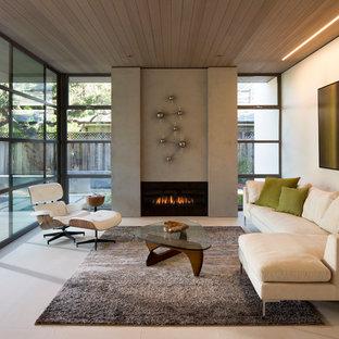 Ejemplo de salón para visitas abierto, moderno, de tamaño medio, sin televisor, con chimenea tradicional y marco de chimenea de hormigón