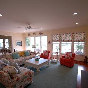 ワシントンD.C.の大きいビーチスタイルのおしゃれなLDK (黄色い壁、無垢フローリング、標準型暖炉、木材の暖炉まわり、壁掛け型テレビ) の写真