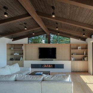 サンフランシスコの中くらいのコンテンポラリースタイルのおしゃれなリビングロフト (白い壁、淡色無垢フローリング、横長型暖炉、ベージュの床、石材の暖炉まわり、埋込式メディアウォール) の写真