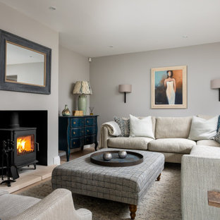 This is an example of a large nautical formal enclosed living room in Gloucestershire with grey walls and a wood burning stove.