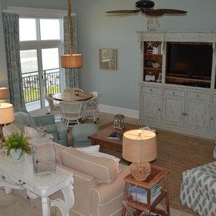 アトランタの中サイズのビーチスタイルのおしゃれな独立型リビング (青い壁、ライムストーンの床、暖炉なし、埋込式メディアウォール、ベージュの床) の写真