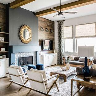 オースティンの中くらいのトランジショナルスタイルのおしゃれな独立型リビング (マルチカラーの壁、無垢フローリング、標準型暖炉、金属の暖炉まわり、壁掛け型テレビ、ベージュの床) の写真