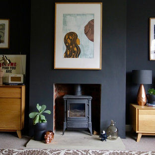 Inspiration for a medium sized midcentury enclosed living room in Other with black walls, carpet, a wood burning stove and a freestanding tv.