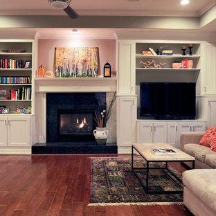 Idee per un soggiorno chic di medie dimensioni con pareti grigie, pavimento in legno massello medio, camino classico, cornice del camino in pietra e parete attrezzata