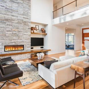 Diseño de salón contemporáneo con paredes blancas, suelo de madera en tonos medios, chimenea lineal y marco de chimenea de piedra