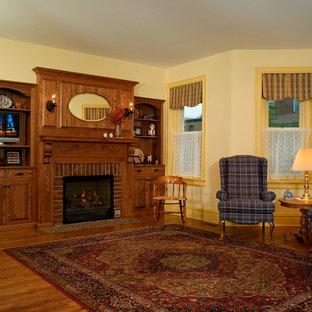 フィラデルフィアの大きいミッドセンチュリースタイルのおしゃれな独立型リビング (フォーマル、黄色い壁、無垢フローリング、標準型暖炉、レンガの暖炉まわり、据え置き型テレビ) の写真