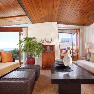 ロサンゼルスの中くらいのトロピカルスタイルのおしゃれなLDK (内蔵型テレビ、茶色い床、濃色無垢フローリング) の写真