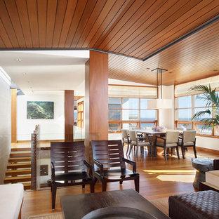 ロサンゼルスの中サイズのトロピカルスタイルのおしゃれなLDK (内蔵型テレビ、茶色い床、濃色無垢フローリング) の写真