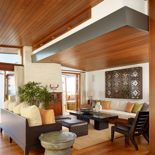 This is an example of a mid-sized tropical open concept living room in Los Angeles with a concealed tv, brown floor and dark hardwood floors.