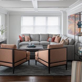 Diseño de salón abierto, actual, de tamaño medio, con paredes blancas, suelo de madera oscura, televisor retractable y suelo marrón