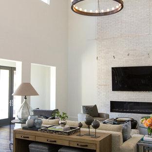 Diseño de salón para visitas tradicional renovado con paredes blancas, suelo de madera oscura, chimenea lineal, marco de chimenea de ladrillo y televisor colgado en la pared