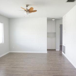 オーランドの小さいミッドセンチュリースタイルのおしゃれなLDK (フォーマル、グレーの壁、磁器タイルの床、暖炉なし、据え置き型テレビ、茶色い床) の写真