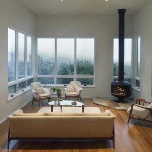 Modelo de salón cerrado, minimalista, de tamaño medio, con paredes blancas, suelo de bambú y estufa de leña