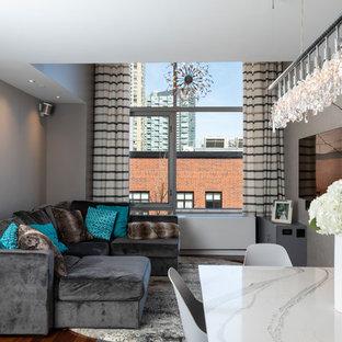Idee per un piccolo soggiorno design aperto con pareti grigie, pavimento in laminato, TV a parete e pavimento marrone