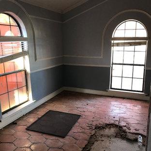 ダラスの広い地中海スタイルのおしゃれなLDK (白い壁、テラコッタタイルの床、両方向型暖炉、レンガの暖炉まわり、壁掛け型テレビ、オレンジの床) の写真