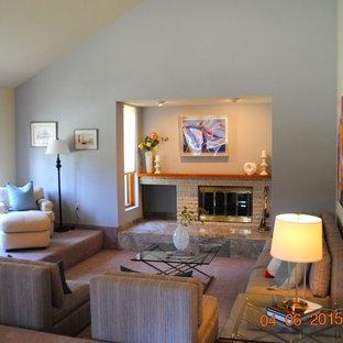 Modelo de salón para visitas cerrado, actual, de tamaño medio, con paredes azules, moqueta, chimenea tradicional, marco de chimenea de ladrillo y suelo rosa